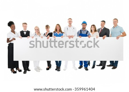 Group portrait of people with various occupations holding blank billboard against white background - stock photo