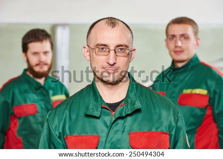 Group portrait of service repairman in uniform in automobile service station garage - stock photo