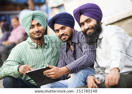 Group portrait of smiling authentic native indian punjabi sikh men in turban with bushy beard - stock photo
