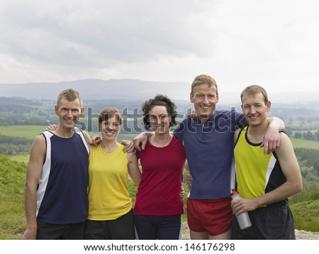 Group portrait of smiling hikers with arms around on country landscape - stock photo