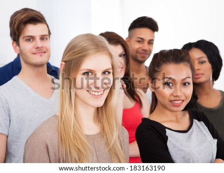 Group portrait of smiling multiethnic college students standing together in classroom