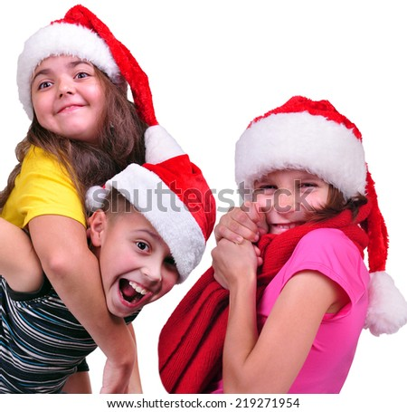 group portrait of three happy playful children with Santa Claus red hats. Christmas, New Year celebration concept - stock photo