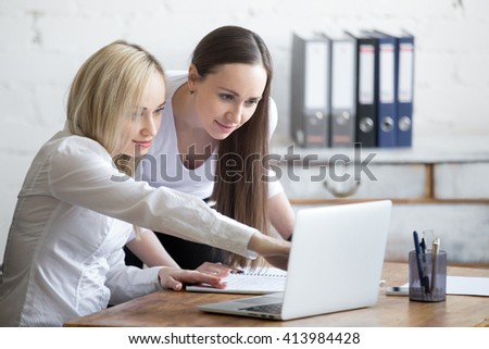 Group portrait of two beautiful smiling young office women looking at laptop screen on office desk. Attractive cheerful business ladies in formal wear using computer while discussing project - stock photo