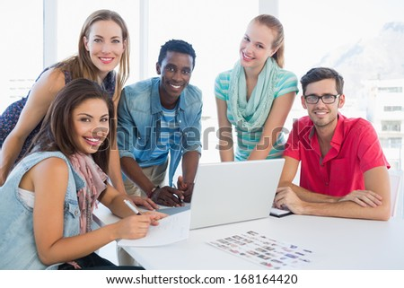 Group portrait of young casual people using laptop in a bright office - stock photo