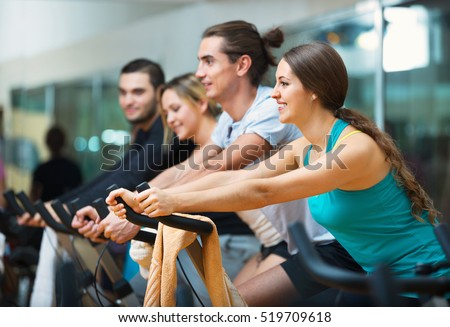 Group positive smiling working out of cycling in modern fitness club