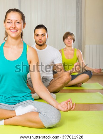 Group practicing yoga class in sport club - stock photo