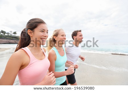Group running on beach jogging. Exercising runners and friends training outdoors living healthy active lifestyle. Multiracial fitness runner people working out together outside smiling happy. - stock photo