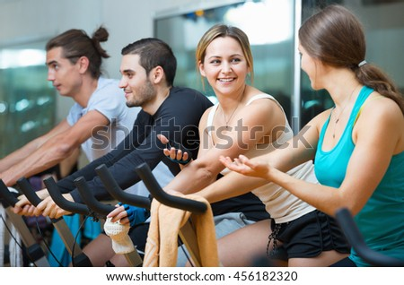 Group smiling  working out of cycling in modern fitness club