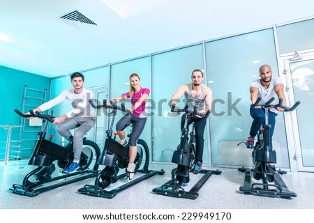 Group sports. Four friends pedal on a stationary bike at the gym - stock photo