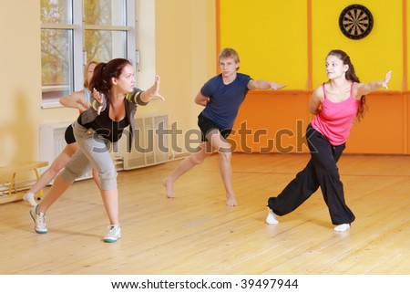 Group stretching out forward at aerobics training in gym