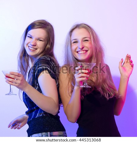 Group stylish women standing in a row toasting with flutes of champagne