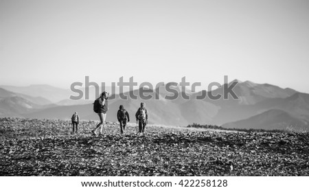 Group/team of four young athletic tourists walking on the rocky mountain plato on their backpacking trip. Woman is talking on the phone. Beautiful mountains on background. black and white
