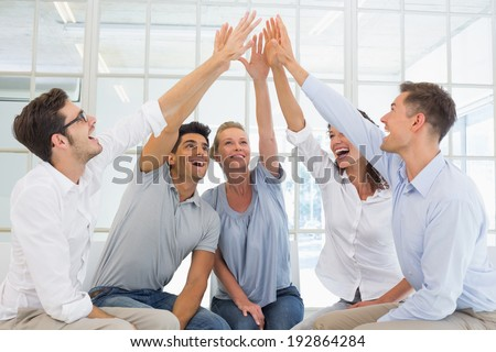 Group therapy in session sitting in a circle high fiving in a bright room - stock photo