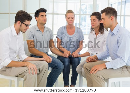 Group therapy in session sitting in a circle holding hands in a bright room - stock photo