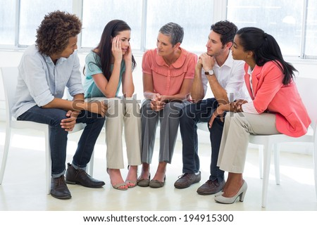 Group therapy in session sitting in a circle in a bright room - stock photo