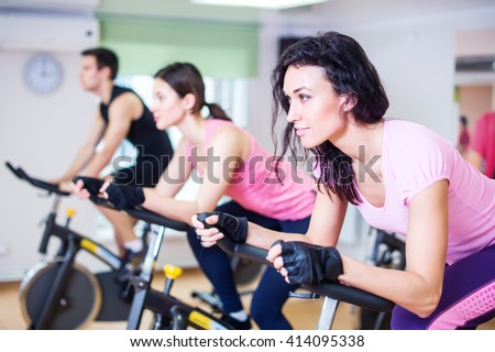 Group training people biking in the gym, exercising legs doing cardio workout cycling bikes. - stock photo