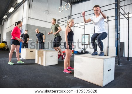 Group trains box jumps - stock photo