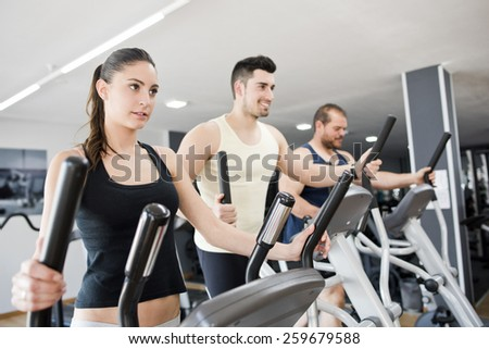 Group with young woman and men on elliptical stepper trainer exercising in gym - stock photo