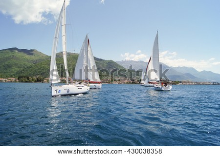 """Group yachts on the water. Tivat, Montenegro - 26 April, 2016. Regatta """"Russian stream"""" in God-Katorskaya bay of the Adriatic Sea off the coast of Montenegro. - stock photo"""