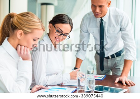 Group young business people sitting in office and holding meeting - stock photo