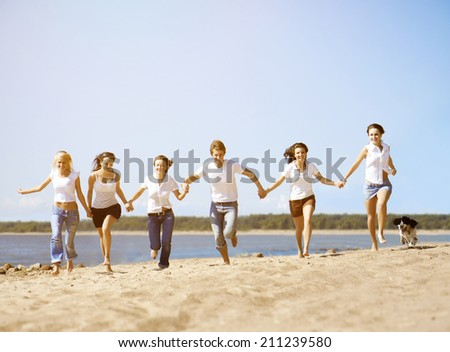 Group young friends enjoying a beach party on vacation. People having fun on beach against the sea on holidays. Group of happy young people dancing, jumpimg and spraying at the beach on summer sunset  - stock photo