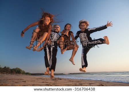 Group young girls in scary skeleton and wild savage costumes jumping high in air with fun before Halloween night party on sunset sea beach. Active people, lifestyles and event celebrations on holidays - stock photo