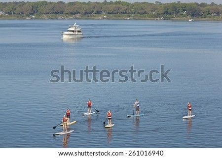 groupl of people stand up paddleboarding - stock photo