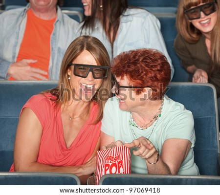 Groups of people in the audience with 3D glasses and laughing - stock photo