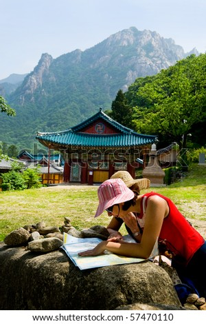 groups of travelers examining map in the Buddhist Sinheungsa Temple in Seoraksan National Park, South korea - stock photo