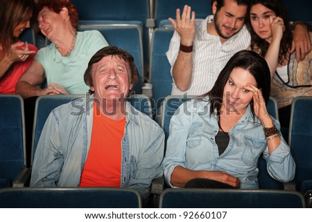 Groups of weeping and embarrassed people in a theater - stock photo