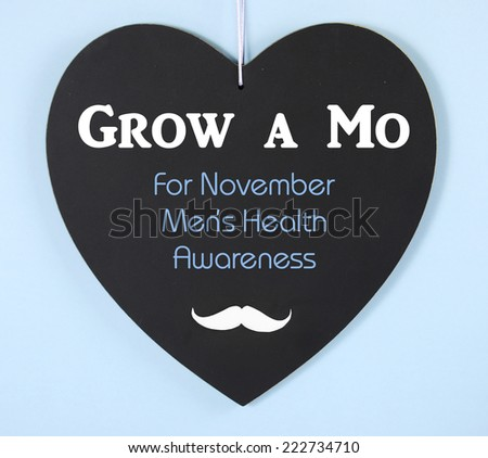 Grow a Mustache message on heart shaped blackboard for November Mens Health Issues Awareness - stock photo