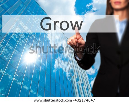 Grow - Businesswoman hand pressing button on touch screen interface. Business, technology, internet concept. Stock Photo