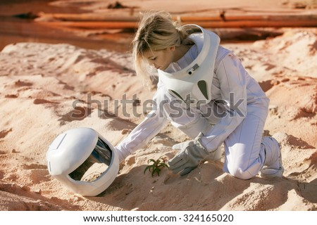 Grow plants on Mars, futuristic astronaut without a helmet,  another planet, image with the effect of toning - stock photo