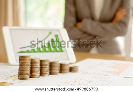 Grow up coins stack with business and finance graph screen on laptop computer on desk of investor adviser. Businesswomen background
