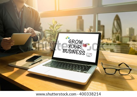 GROW YOUR BUSINESS CONCEPT Thoughtful male person looking to the digital tablet screen, laptop screen,Silhouette and filter sun - stock photo