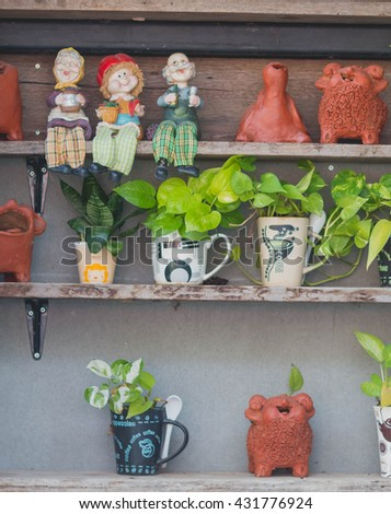 Growing basil in a flowerpot at home. Garden tools for pot plants: shovel, rake and scissors - stock photo