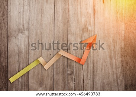 GROWING GRAPH LINE  BUSINESS PAPER ARROW ON WOODEN BACKGROUND BUSINESS CONCEPT