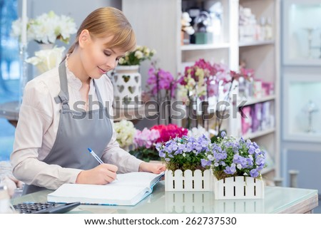 Growing her flower business. Young attractive florist making notes at her note pad sitting by the counter of the flower shop - stock photo