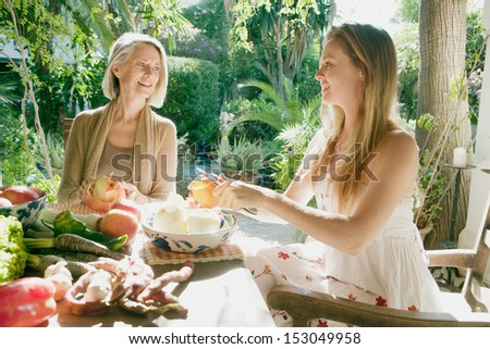 Grown up daughter and mother sitting together in a home garden peeling apples and preparing vegetables and healthy organic food during a sunny day, having a conversation. - stock photo