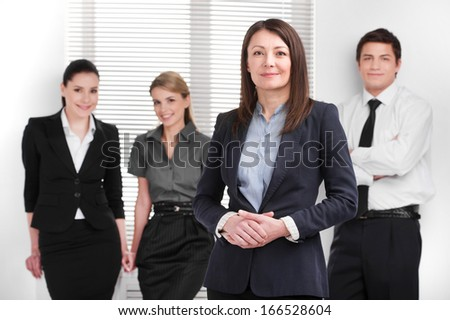 Grown up Successful business woman holding hands together. Young Smiling business people standing on blur background  - stock photo