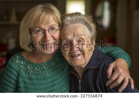 Grown woman with her old mother. - stock photo