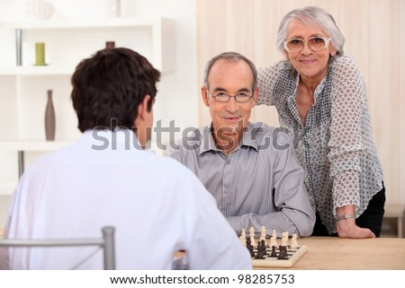 Grownup family playing chess