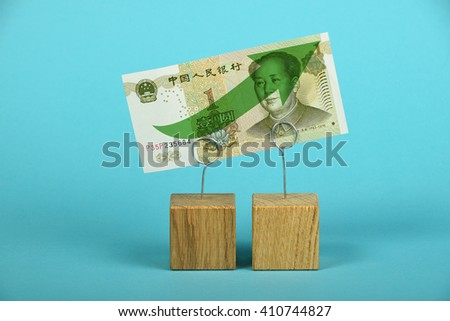 Growth and support of Chinese economy and yuan, one yuan banknote with green arrow up on two holders over blue background