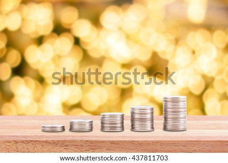 growth chart from coins stack on table top on light yellow bokeh background