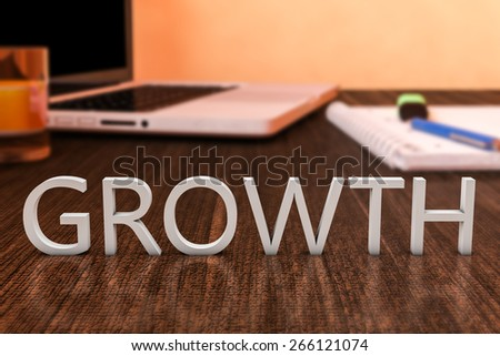 Growth - letters on wooden desk with laptop computer and a notebook. 3d render illustration. - stock photo