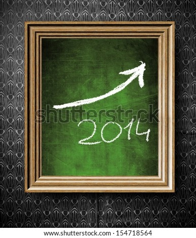 Growth trend of 2014 with copy-space chalkboard in old wooden frame on vintage wall - stock photo