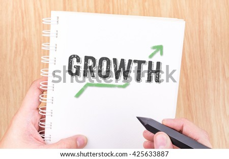 Growth word on white ring binder notebook with hand holding pencil on wood table,Business concept.