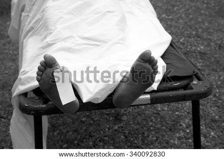Gruesome image of a dead persons feet with a toe tag to identify the person and cause of death, next of kin and any other important information. - stock photo