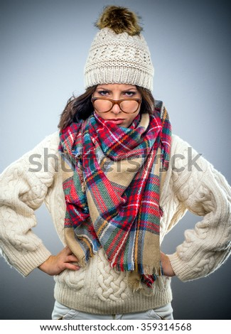 Grumpy attractive young woman in winter fashion wearing a colorful scarf and glasses perched on her nose, glaring at the camera with her hands on her hips - stock photo