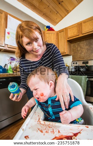 Grumpy baby in kitchen is being fed from her bottle - stock photo